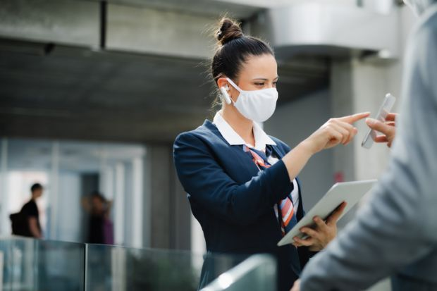 flight attendant talking to businessman on airport, wearing face mask