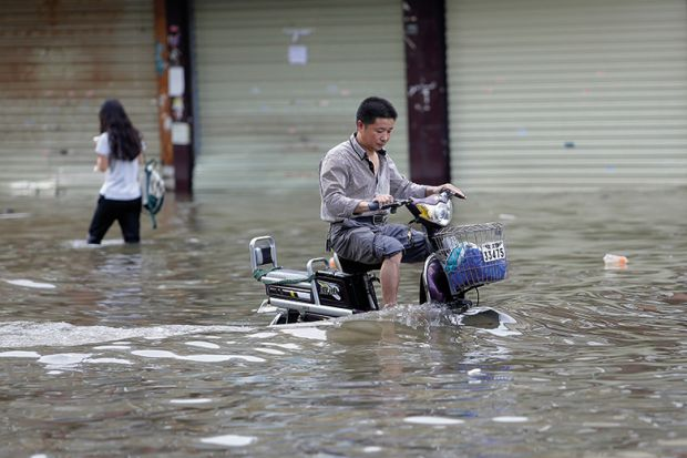 Man riding a bicycle in flood