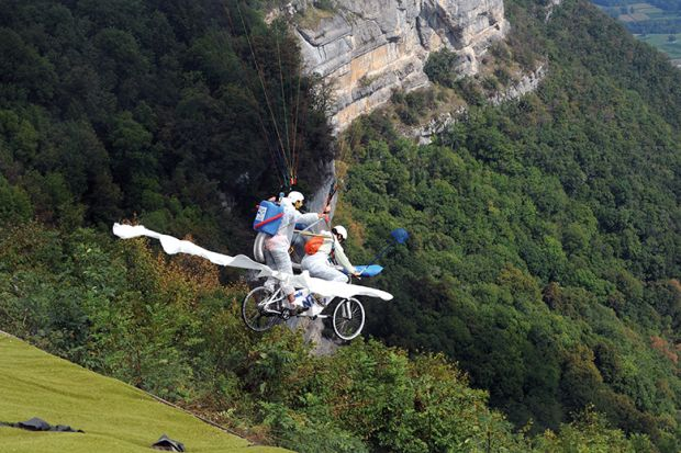 """Paragliders compete on their """"tandem bicycle"""" in Saint-Hilaire du Touvet, France, 2012, illustrating entrepreneurship"""