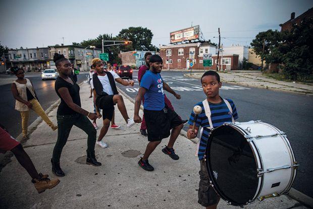 Children dancing in street, following a drummer