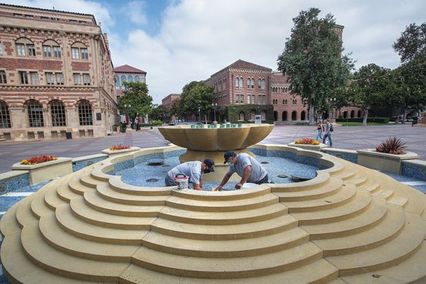 Men repair damaged tiles inside a fountain on the USC campus in Los Angeles
