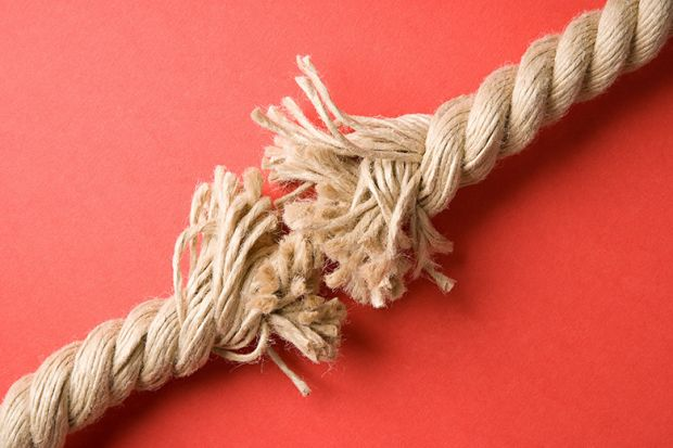 Frayed rope on red background