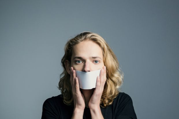 A man holds paper in front of his mouth, symbolising non-disclosure agreements