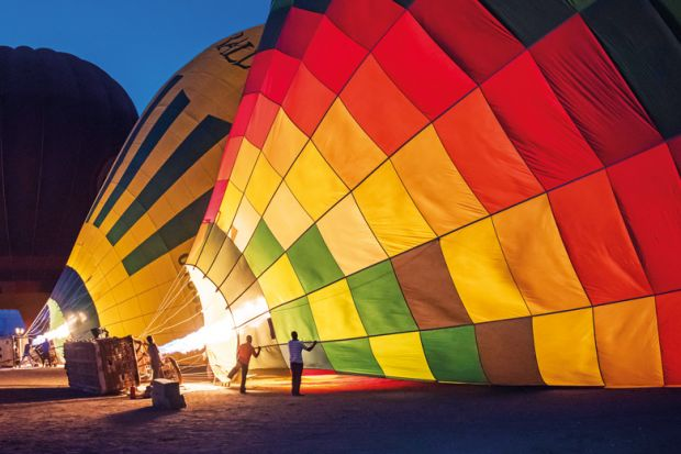 Gas burners filling hot air balloons at dawn