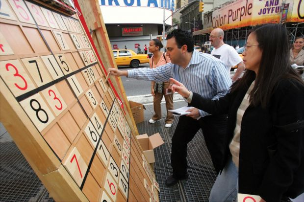 Jim Ressler, owner of Sudoku Board USA, helps Dorris Lam of Glen Rock, N.J., solve a Sudoku puzzle on a gigantic board in Times Square
