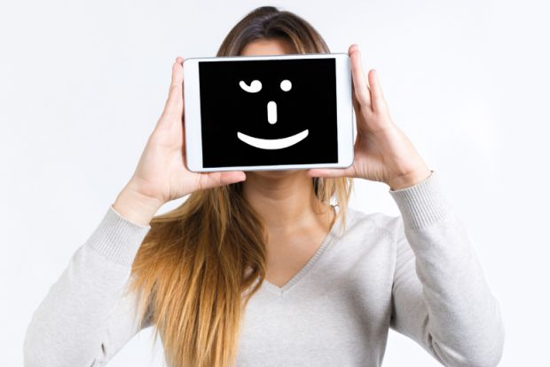 Girl holding a tablet computer with a smiley face on it