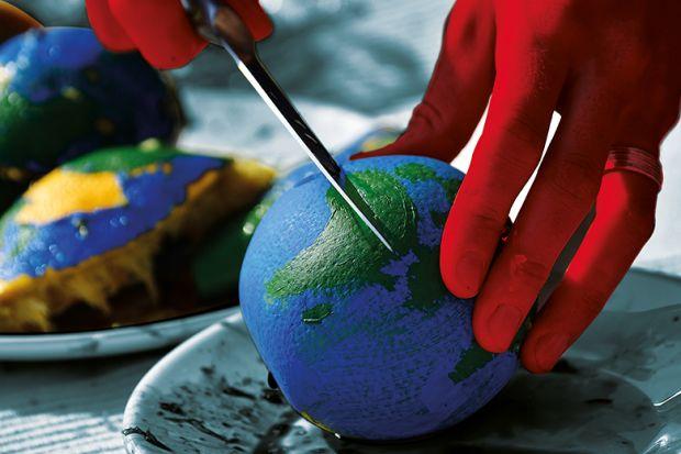 Cutting an orange painted like a globe representing funding cuts