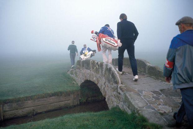 Golfers crossing a bridge in fog