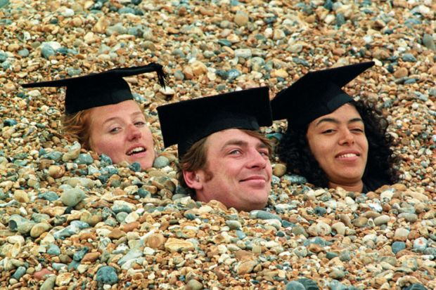 Graduates buried in shingle on Brighton beach, England