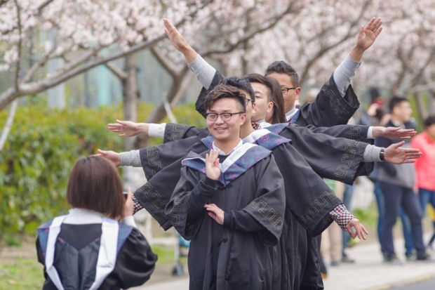 Graduating students taking photos in cherry festival in Tongji University.
