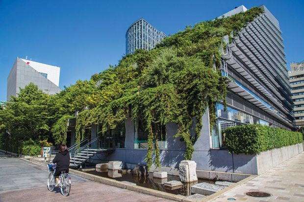woman cycles past modern building in Japanese city with green roof of plants