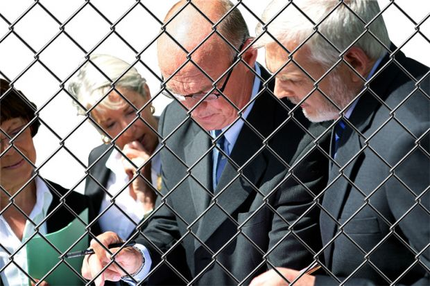 Group of academics in conversation behind chainlink fence