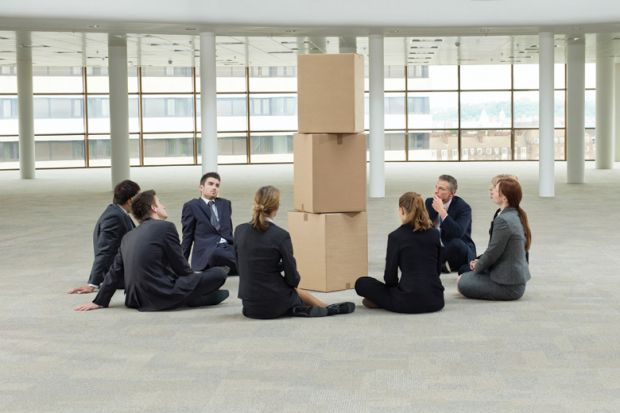 Group of businesspeople sat around pile of cardboard boxes