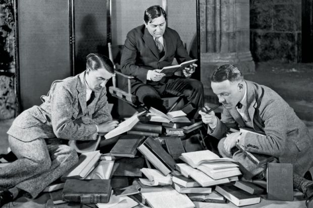 Group of men reading pile of books