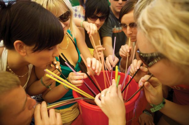 Group of women drinking through straws from bucket