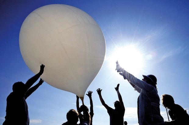 Group of people push balloon into the air