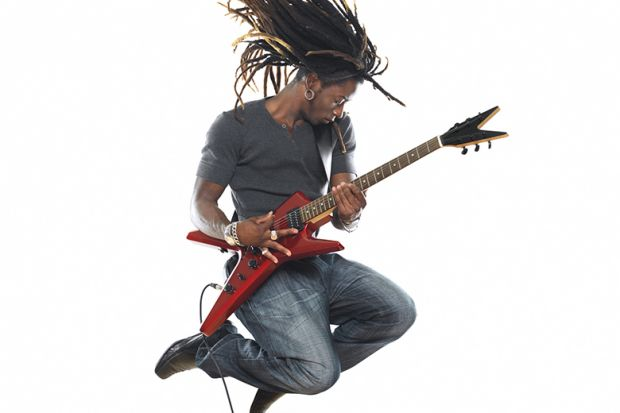 Musician leaps in air while playing electric guitar