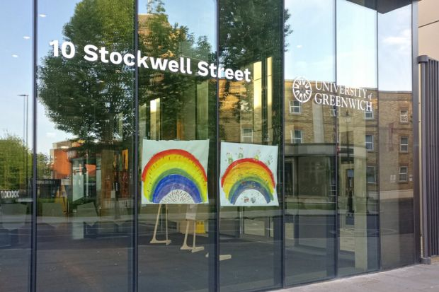 Hand drawn rainbow expressing thank to NHS and key workers displayed at glass window University of Greenwich during coronavirus outbreak