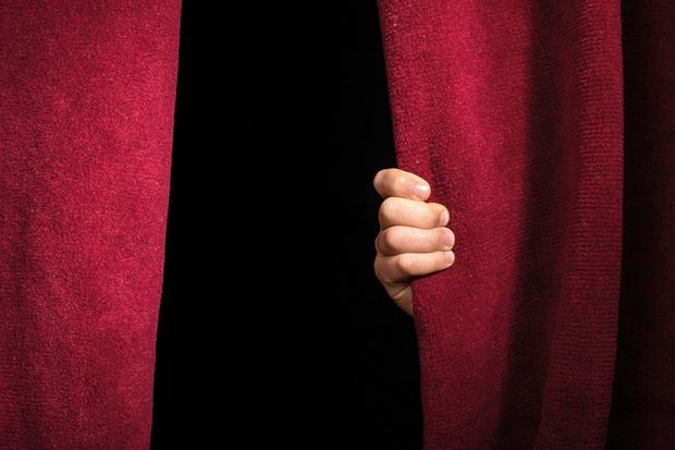 A hand on a theatre curtain