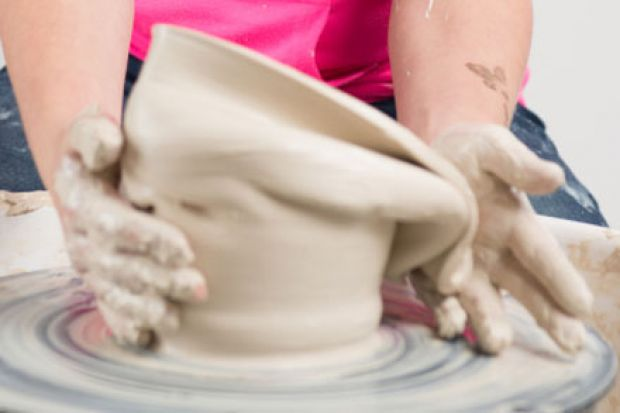 Hands working clay on potter's wheel