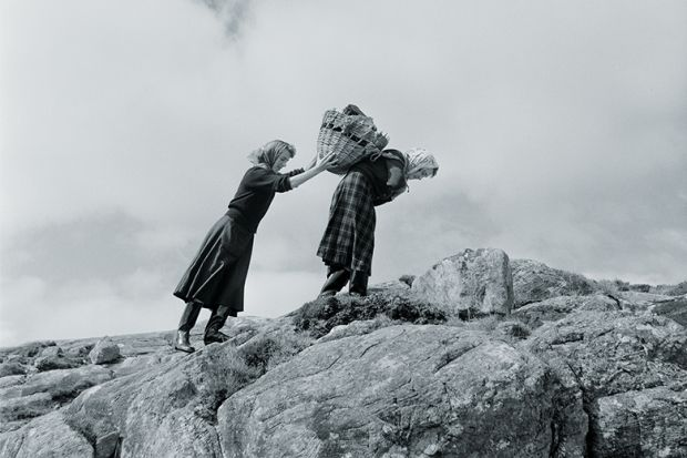 Two women carry heavy parcels