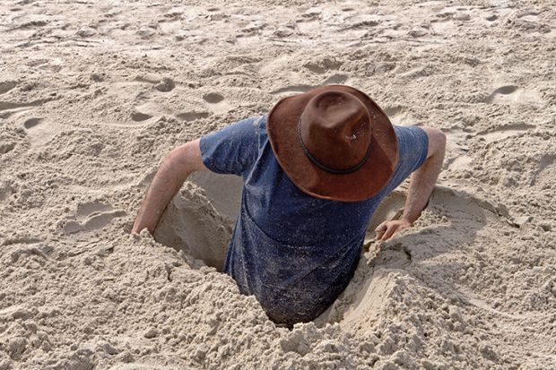 Man buried to waist in sand