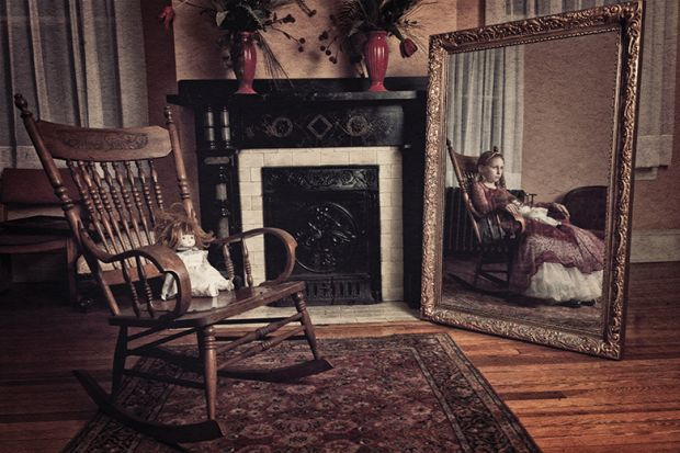 Doll in chair with girl in mirror reflection