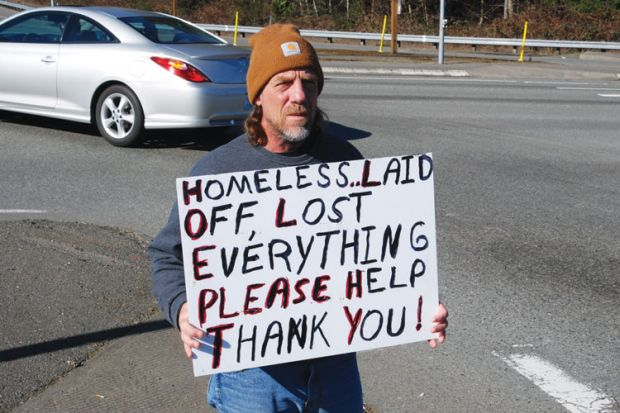 Homeless man on street corner holding sign