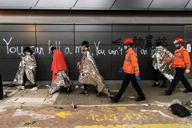 Hong Kong students walk past graffiti