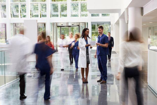 A group of people inside a hospital entrance
