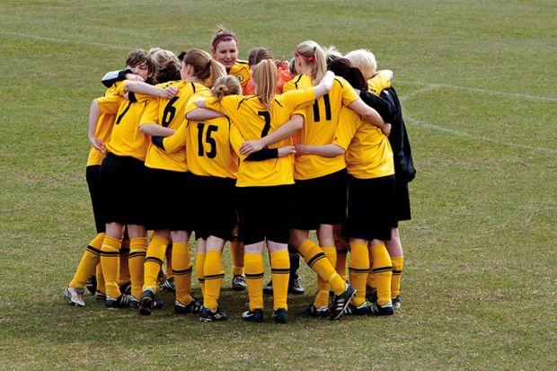 Women`s football team huddle before match