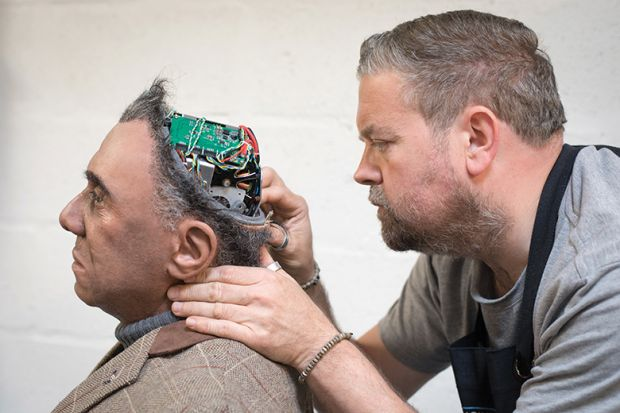 Engineered Arts prosthetic expert Mike Humphrey checks on Fred, a Mesmer robot built at the company's headquarters in Penryn, Cornwall