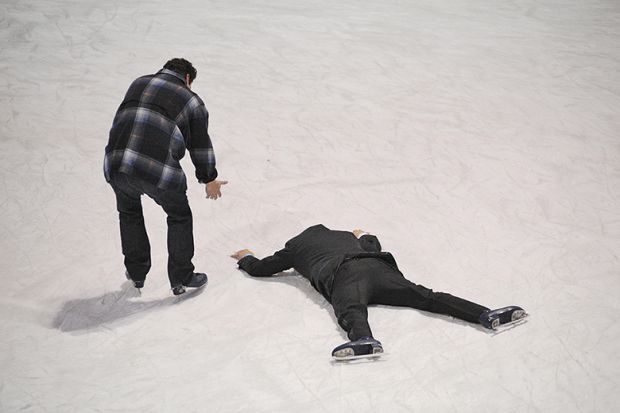 Man helps fellow skater who has fallen on the ice