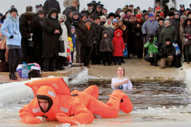 A rescue worker exits the icy waters of the Dnepr River in Kiev during an Orthodox Epiphany celebration