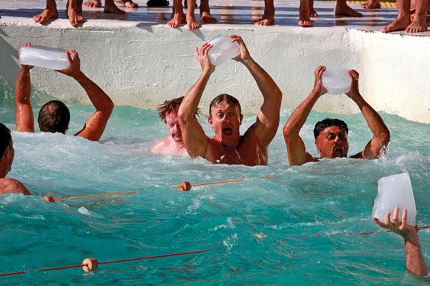 Swimmers holding ice cubes aloft