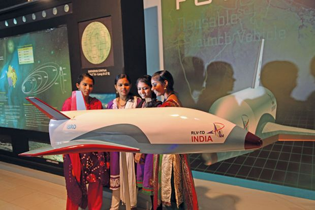 indian women next to indian space shuttle