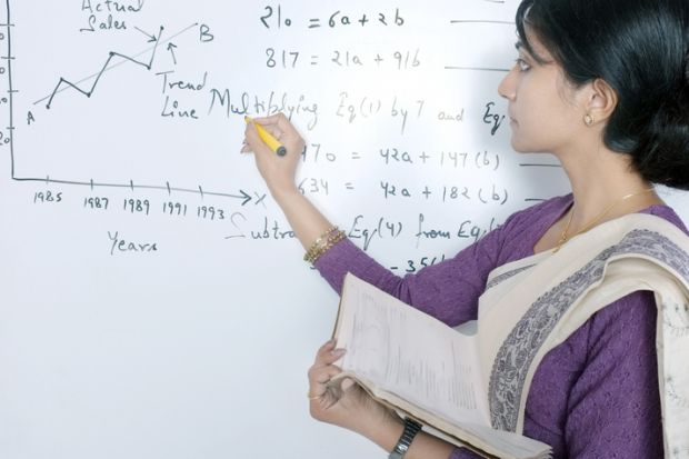 An Indian academic writes formulas on a whiteboard