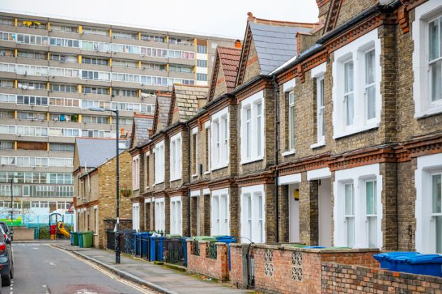 Traditional English terraced houses with huge council block in the background