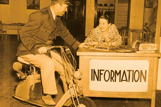 Man on scooter talks to woman at information desk
