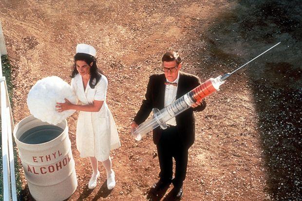 Nurse and man holding giant syringe