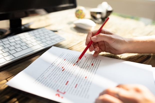 Person marking an error on a page with red marker