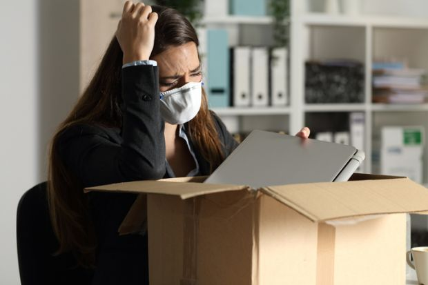 A woman packs her things after being fired