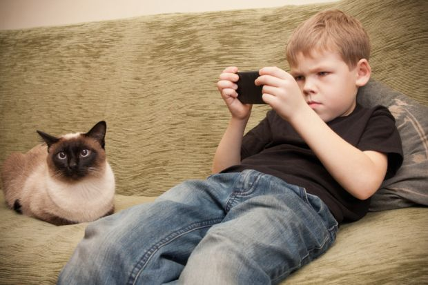 Boy playing Candy Crush on sofa