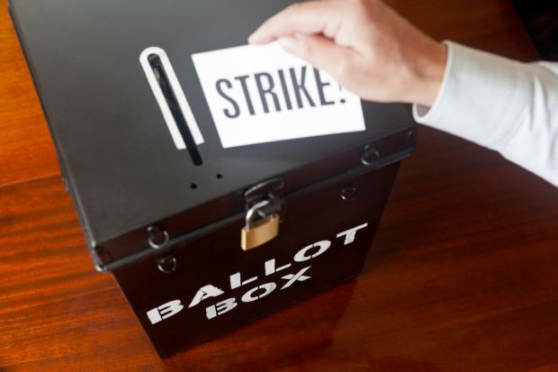 man placing strike ballot card into box