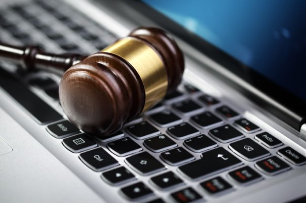 Judge's gavel on computer keyboard