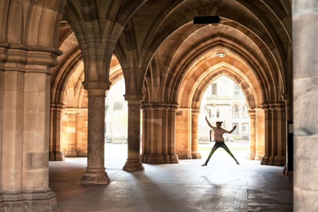 Girl jumping in cloisters of University of Glasgow