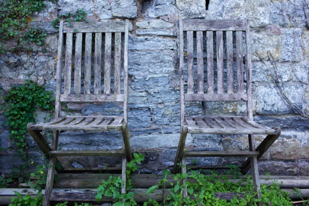 Pair of empty, aged wooden chairs