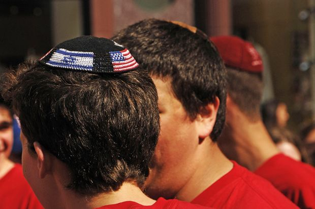 Young man wearing yarmulke with American and Israeli flags