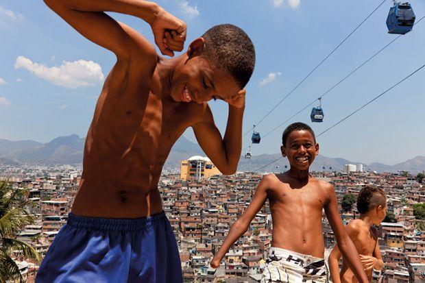 Children play near cable cars that cross over Complexo do Alemao in Rio de Janeiro, Brazil