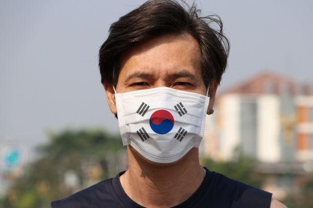 Man wearing a mask with the South Korean flag